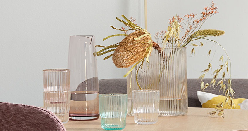 Jug, drinking glasses, and vases all in coloured glass